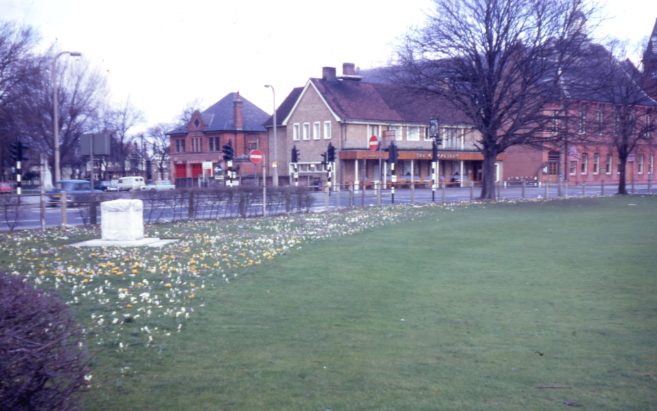 Corner of Cricket Green, Mitcham, Surrey CR4. Tom Ruff memorial and crocuses. the Vestry Hall in background.