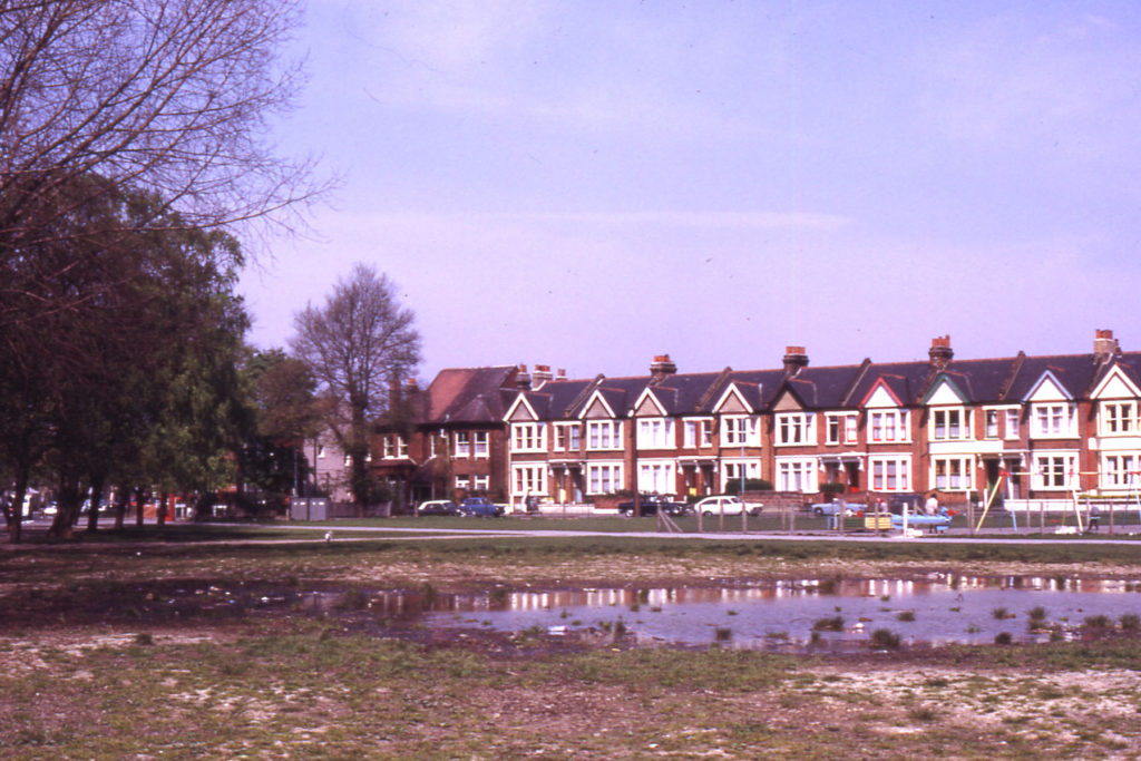 Figges Marsh with Gorringe Park Avenue in background, Mitcham, Surrey CR4. Pond forming on site of old air-raid shelter and earlier pond. Little Graveney ran along eastern (right-hand) side of Marsh