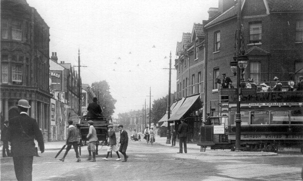 Postmarked 1907, the year in which Wimbledon saw its first trams, this view looks up Merton Road. A LUT tram is swinging round from Merton High Street. It advertises Skewes' store in Wimbledon, as well as Sandown Park Races.